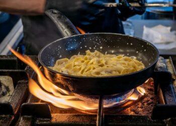 Chef che cucina tagliatelle e verdure in padella sul fuoco